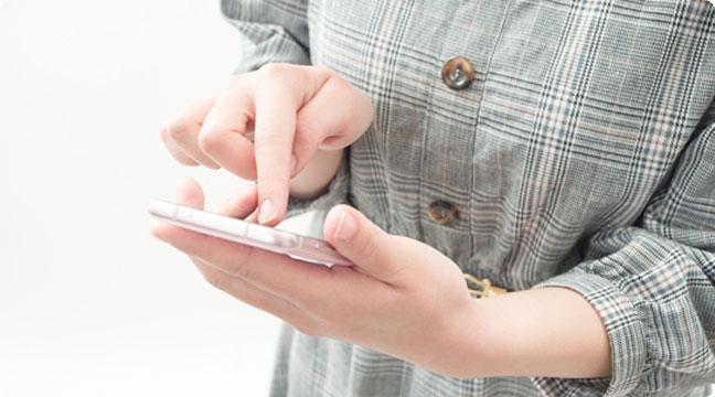 スマートフォンでご依頼の電話をする女性の手元