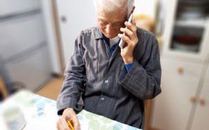 電話で問い合わせする年配男性